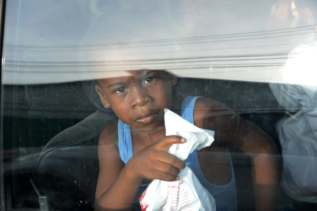 A young boy looks out of a car window upon arriving to San Pedro Sula, 240 kms north of Tegucigalpa, on July 2, 2014, after being deported from the US. Thousands of unaccompanied children, most of them from Central America, have trekked to the United States in recent months and now face deportation in what the United States has called a humanitarian crisis.
