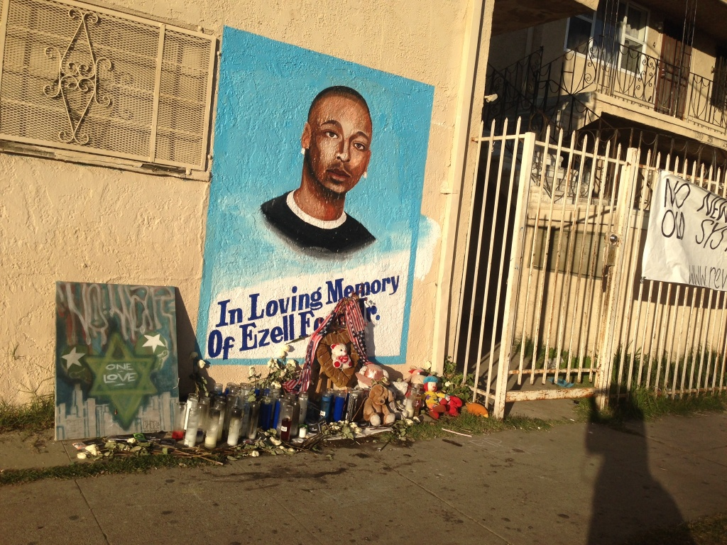 A portrait of Ezell Ford, killed by LAPD officers in August 2014 near this spot, is on the wall of a market at 65th Street and Broadway in South Los Angeles