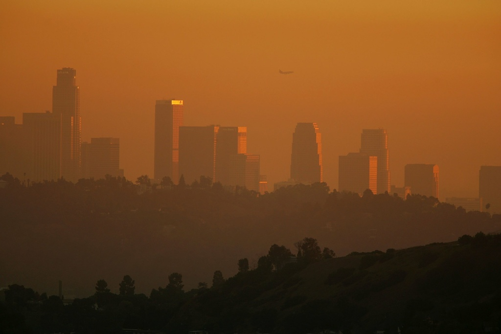 The downtown skyline is enveloped in smog shortly before sunset in Los Angeles, California.