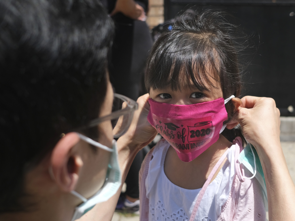 A girl in Jersey City wears a mask at her Pre-K graduation ceremony almost a year ago. Now schools are deciding how looser CDC guidelines on masks affect education.