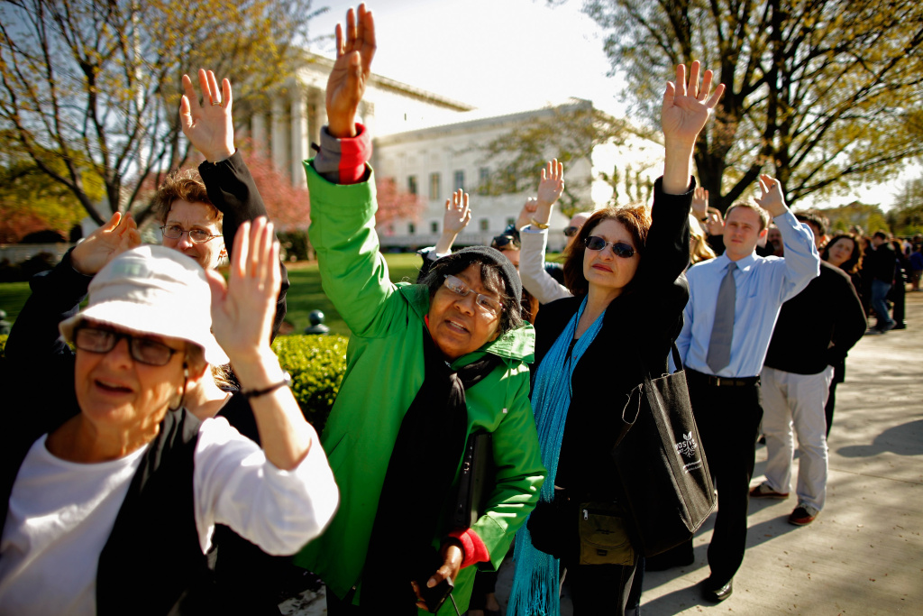 People raise their hands in hope of getting a ticket to view oral arguments in the Patient Protection and Affordable Care Act outside the Supreme Court March 26, 2012, in Washington, DC. Today the high court, which has set aside six hours over three days, will hear arguments over the constitutionality of the act.