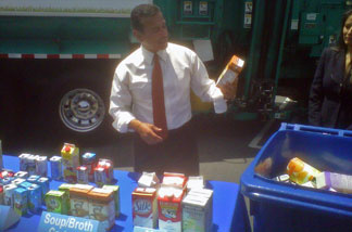 Los Angeles Mayor Antonio Villaraigosa tosses food and beverage cartons into a recycling bin near Fresco Community Market in L.A.