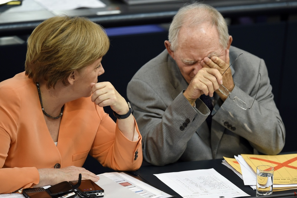 German Finance Minister Wolfgang Schaeuble (R) and German Chancellor Angela Merkel chat during a session at the Bundestag lower house of parliament on the Greek crisis on July 1, 2015 in Berlin.