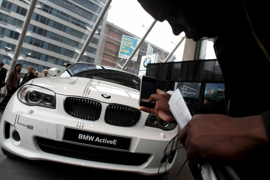 A man takes a picture of the new BMW electric car the ActiveE on April 18, 2011 in New York City. The BMW ActiveE, which will be available for lease in select markets beginning in Fall 2011, is BMW`s second electric vehicle. The ActiveE has an output of 170 horsepower and has a range of around 25 miles after just a one-hour charge at the wallbox and can fully charged within four to five hours.
