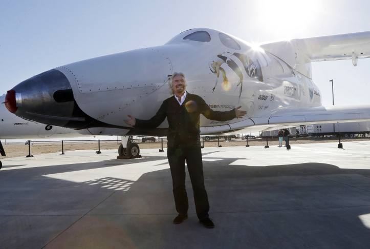 In this Sept. 25, 2013, file photo, British entrepreneur Richard Branson poses with the first SpaceShipTwo at a Virgin Galactic hangar at Mojave Air and Space Port in Mojave, Calif. Virgin Galactic will roll out a new copy of its space tourism rocket Friday, Feb. 19, 2016, as it prepares to resume flight testing for the first time since a 2014 accident destroyed the original and killed one of its two pilots.