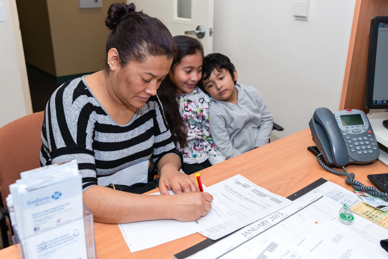 Guadalupe Carrera, 36, with her daughter Eva Maqueda, 9, and son Jose Maqueda, 5, fills out an application for health insurance assistance at El Proyecto Del Barrio Family Health Care Clinic in 2015.