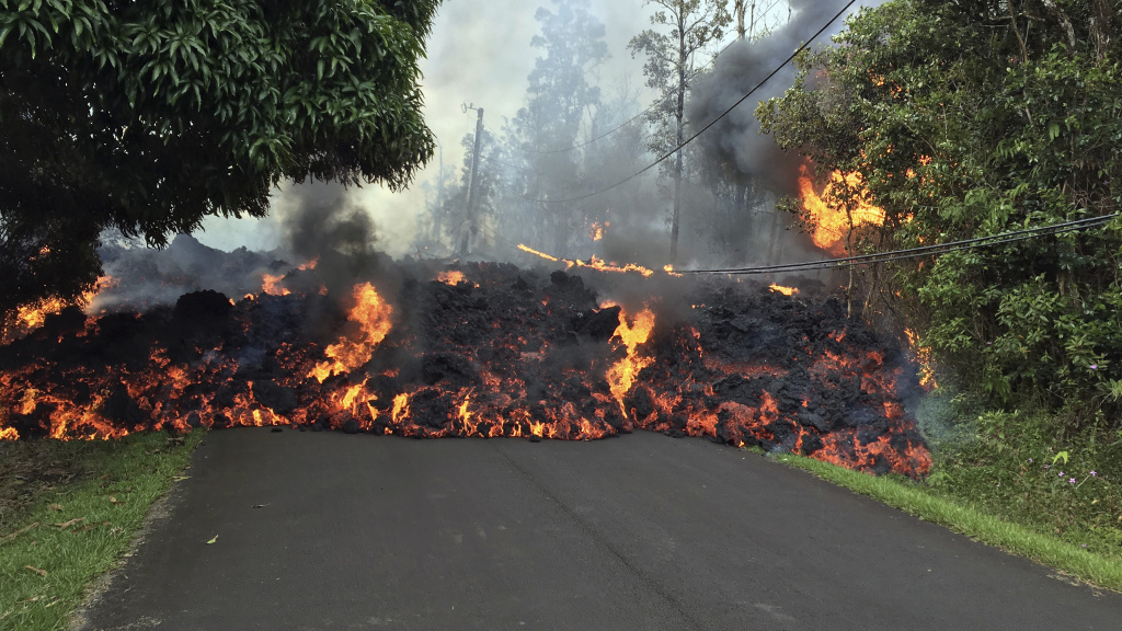 In this Sunday, May 6, 2018 photo provided by the U.S. Geological Survey, a lava flow moves across Makamae Street in the Leilani Estates subdivision near Pahoa on the island of Hawaii. Kilauea volcano has destroyed more than two dozen homes since it began spewing lava hundreds of feet into the air last week. (U.S. Geological Survey via AP)