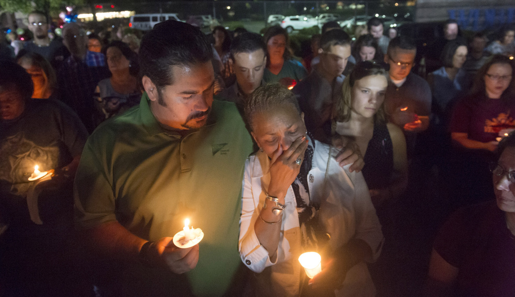 Roanoke City Council member Anita Price, right, is comforted by friend Jan DeVries as they show their community support at a candlelight vigil in front of the studios of WDBJ-TV in Roanoke, Va., Thursday, Aug. 27, 2015, a day after reporter Alison Parker and cameraman Adam Ward from the station were killed during a live broadcast. (AP Photo/Don Petersen)