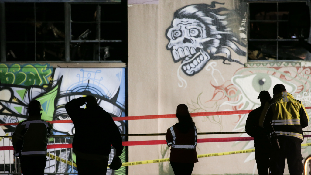 On Monday, workers and emergency responders look at a warehouse in which a fire late Friday claimed the lives of at least 36 people on in Oakland, Calif.