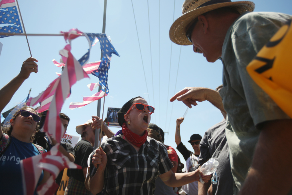 A protester who opposes arrivals of buses carrying largely women and children undocumented migrants for processing at the Murrieta Border Patrol Station and a counter-demonstrator (L) face off on July 4, 2014 in Murrieta, California. Earlier this week, protesters in the city turned away buses carrying about 140 immigrants that had been apprehended in Texas and flown to California for processing as Texas deals with an influx of immigrants. Federal officials estimate more than 50,000 minors, mostly from Central America, have been caught crossing the border since October 2013.