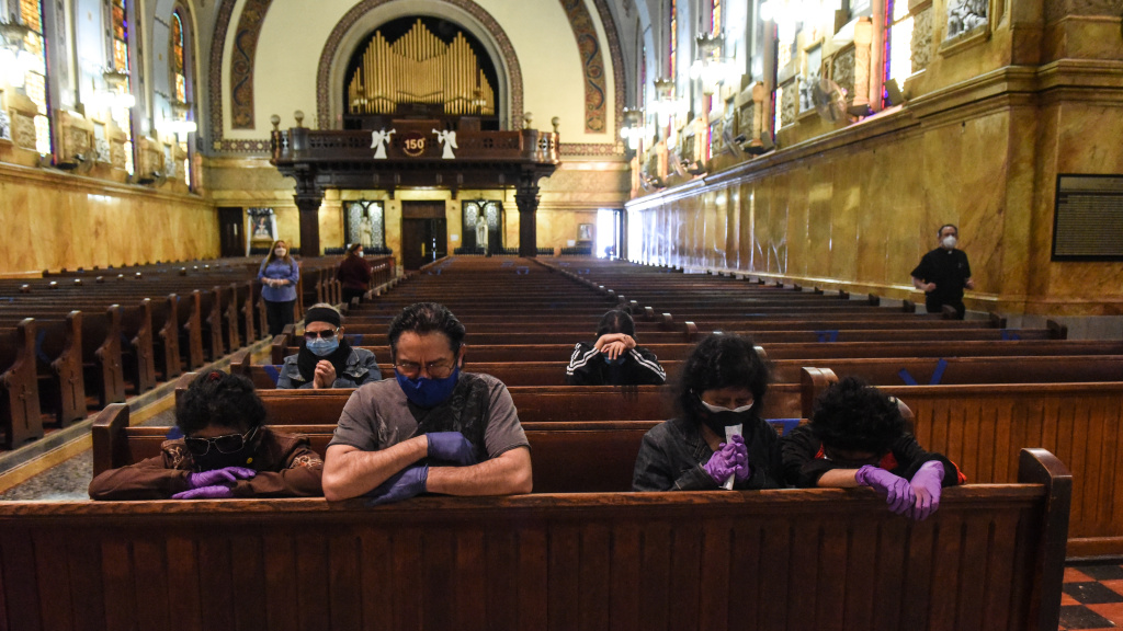 People pray inside St. Michael's Church on Tuesday in Brooklyn.