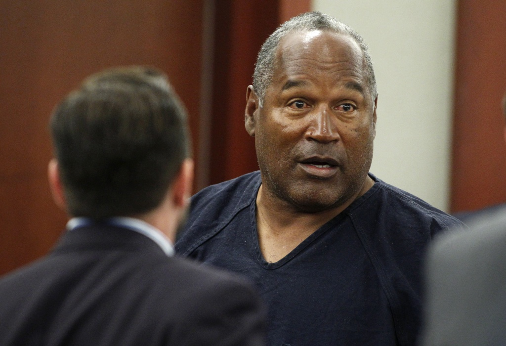 O.J. Simpson should know next week whether his blemish-free record behind bars and contrition for trying to take back sports memorabilia of his glory days will win him favor with the Nevada Board of Parole Commissioners. (File photo: O.J. Simpson (R) stands at the end of a hearing in Clark County District Court on May 17, 2013 in Las Vegas, Nevada).
