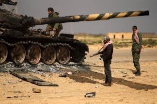 Libyan rebels gather around a burning T-72 tank belonging to forces of Libyan leader Moamer Kadhafi, which were targeted the day before by a French air strike, in Shat al-Bedin 50 kms West of Benghazi.