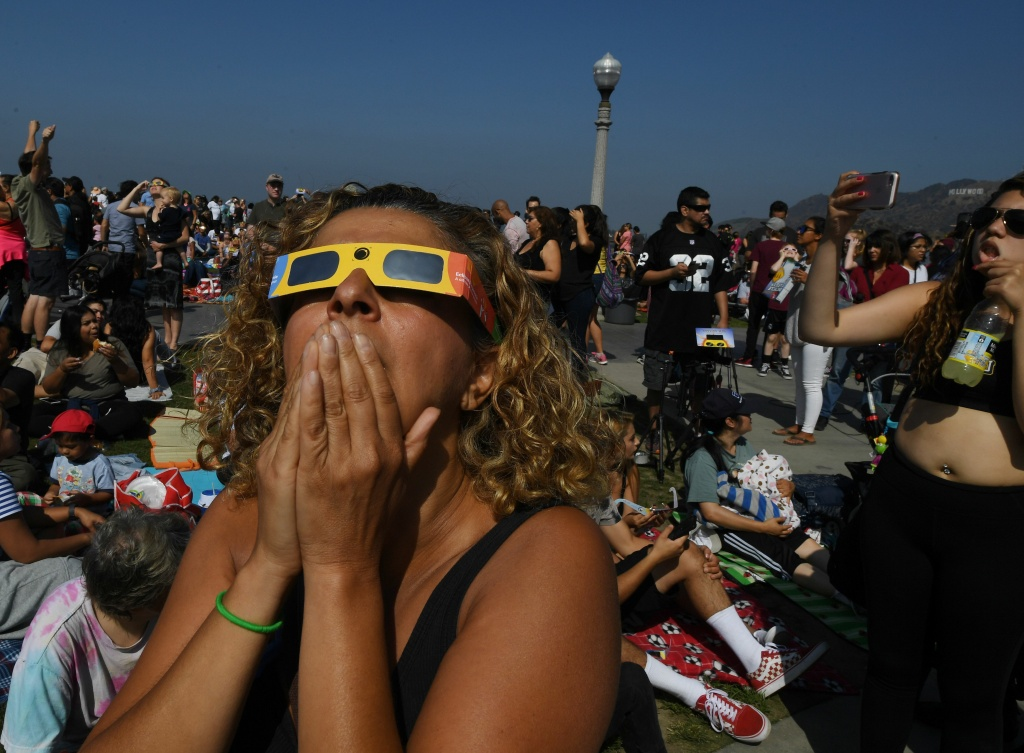 Cherri Haghighit views the start of the total solar eclipse at the Griffith Observatory in Los Angeles, California, on August 21, 2017. Emotional sky-gazers on the US West Coast cheered and applauded Monday as the Sun briefly vanished behind the Moon -- a rare total solar eclipse that will stretch across North America for the first time in nearly a century.     / AFP PHOTO / Mark RALSTON        (Photo credit should read MARK RALSTON/AFP/Getty Images)