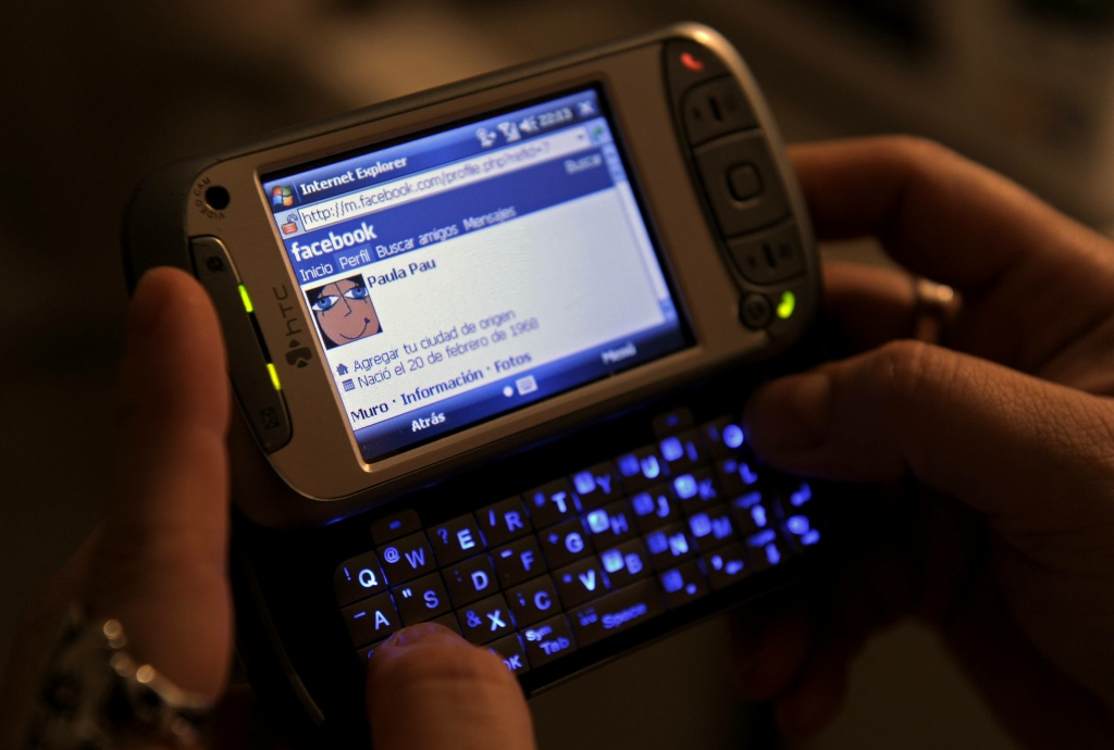 A woman uses her smart phone to acces Facebook.