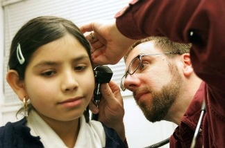 Fourth-grader Arylu Paniagua, 9, receives an ear exam from Dr. Michael Paul during a physical in the Loyola Pediatric Mobile Health Unit, parked outside Columbus West Elementary School, February 22, 2005 in Cicero, Illinois.