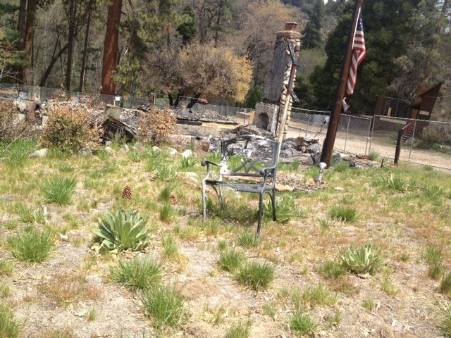 An American flag flies half-staff in the middle of the cabin grounds where Christopher Dorner died near Big Bear. Many items, like furniture and books, have stayed put after the fire burned the walls of the cabin down to its foundation.