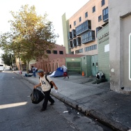 A sign reading 'Skid Row' is painted on a wall next to the Los Angeles Mission, September 22, 2014 in Los Angeles, California. Los Angeles' Skid Row contains one of the largest populations of homeless people in the United States.