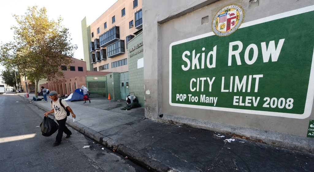 A sign reading 'Skid Row' is painted on a wall next to the Los Angeles Mission, September 22, 2014 in Los Angeles, California. Los Angeles' Skid Row contains one of the largest populations of homeless people in the United States
