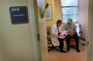 Dr. Olveen Carrasquillo sits with Juan Gonzalez as he conducts a checkup on him at the University of Miami's Miller School of Medicine.