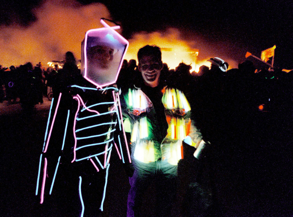 People wearing illuminated costumes walk past the burning remains of a 52-foot tall wooden man on September 2, 2000 during the15th annual Burning Man festival in the Black Rock Desert near Gerlach, Nevada.