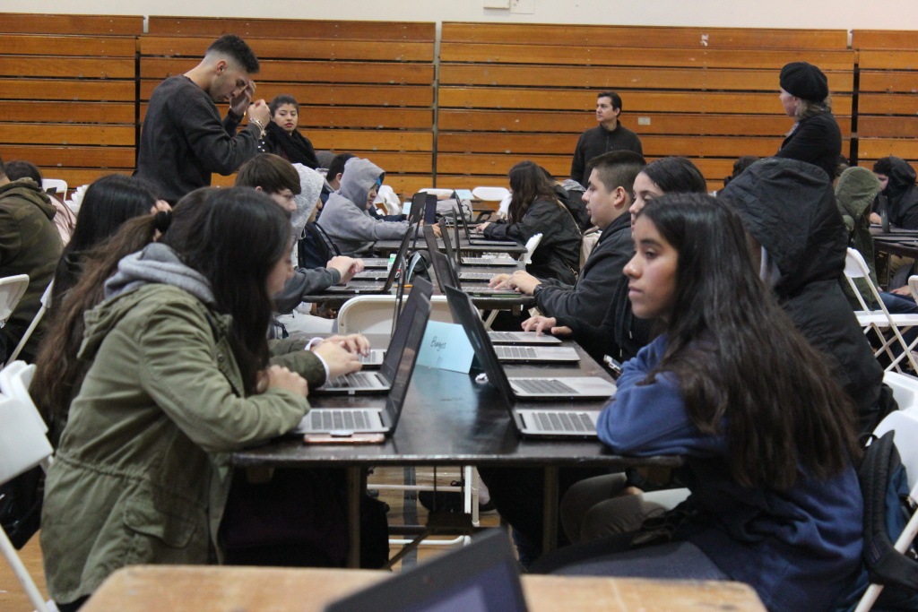 At Reseda Charter High School, students in a gym use school laptops to work on a college application program while their teachers — members of United Teachers Los Angeles — strike.