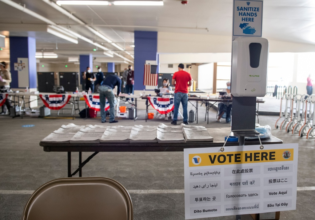 Masks and disinfectant are seen next to electoral booklets displayed in multiple languages at the Beverly Hills City Hall voting center set up in a parking garage on October 28, 2020, in Beverly Hills, California.