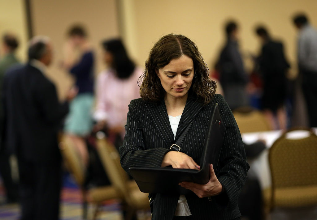 A job seeker goes through a folder before meeting with recruiters at the National Career Fairs' San Francisco South Career Fair in July San Mateo, California.