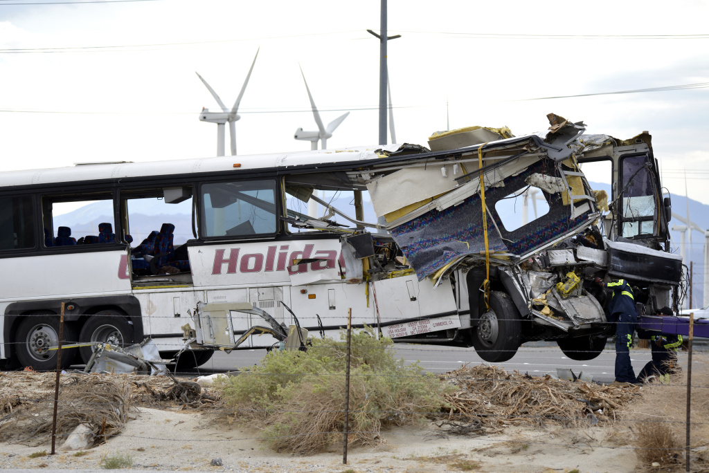 FILE: Workers prepare to haul away a tour bus that crashed with semi-truck on Interstate 10 just west of the Indian Canyon Drive off-ramp, in Desert Hot Springs, near Palm Springs, Calif., Sunday, Oct. 23, 2016.