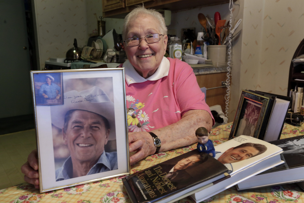 In this Friday, April 1, 2016 photo, former Ronald Reagan International Fan Club president Zelda Multz, 89, poses for photos with Reagan memorabilia in her apartment in the Brooklyn borough of New York. Reagan had an army of star-struck movie fans who wrote him letters - and who to their surprise often got a personal reply. For one writer in particular the replies added up to well more than 100 as Multz evolved from teenage president of the Reagan fan club to a lifelong literary friend of the man who, 40 years after she first wrote to him, became the nation's 40th president. The letters are going on the auction block April 18.