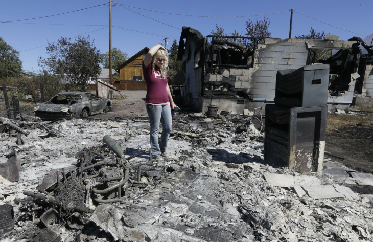 Kathy Besk (L) cries with her daughter Shelley Besk (C) and her son Bryce Shannon (R) after two CalFire firefighters found her rings in the burned-out ruins of their home on September 16, 2014 in Weed, California. Fueled by high winds, the fast-moving Boles Fire swept through the town of Weed yesterday, burning 100 structures that included the high school and a lumber mill.