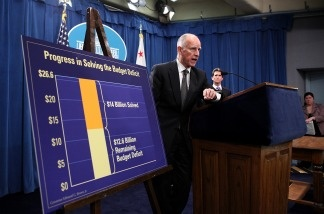 California Gov. Jerry Brown stands next to a chart that shows dollar amounts in the millions that were cut from the State's budget.