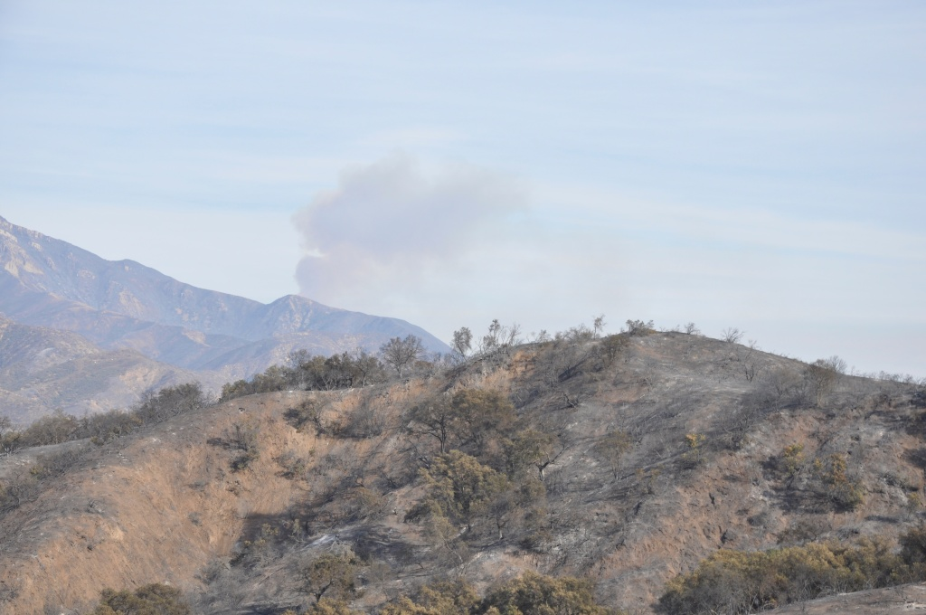 Set against a hillside charred by the Thomas Fire, smoke coming from above the east end of the Ojai Valley was visible on Dec. 18, 2017.