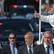 Pope Francis leans out and waves to the crowd as he rides in a popemobile along a parade route around the National Mall on September 23, 2015 in Washington, DC.