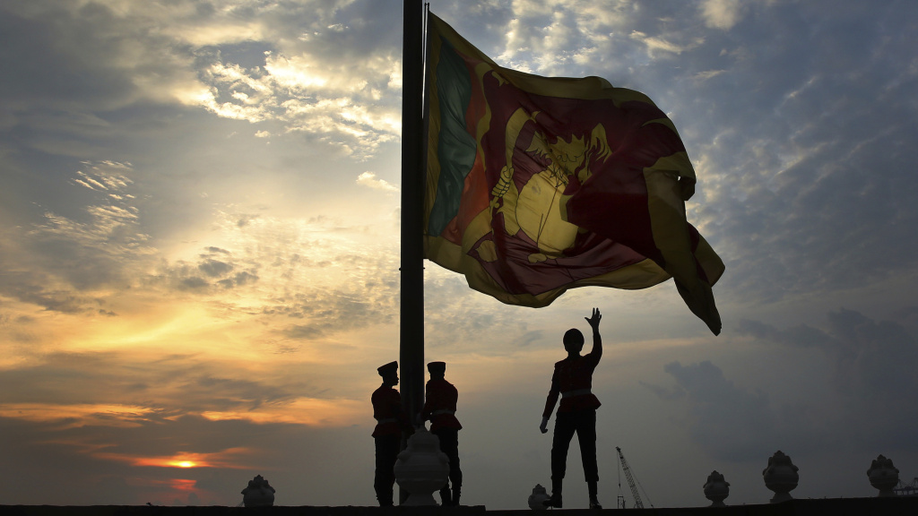 Sri Lankan soldiers lower the national flag in Colombo, Sri Lanka, Sunday. President Maithripala Sirisena banned face coverings under an emergency law that went into effect Monday.