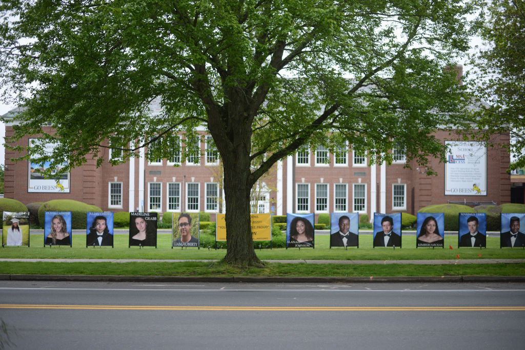 Portrait photographs of graduates of the Bridgehampton High School of 2020 are placed along the road in front of the school building on May 25, 2020, in Bridgehampton, New York.