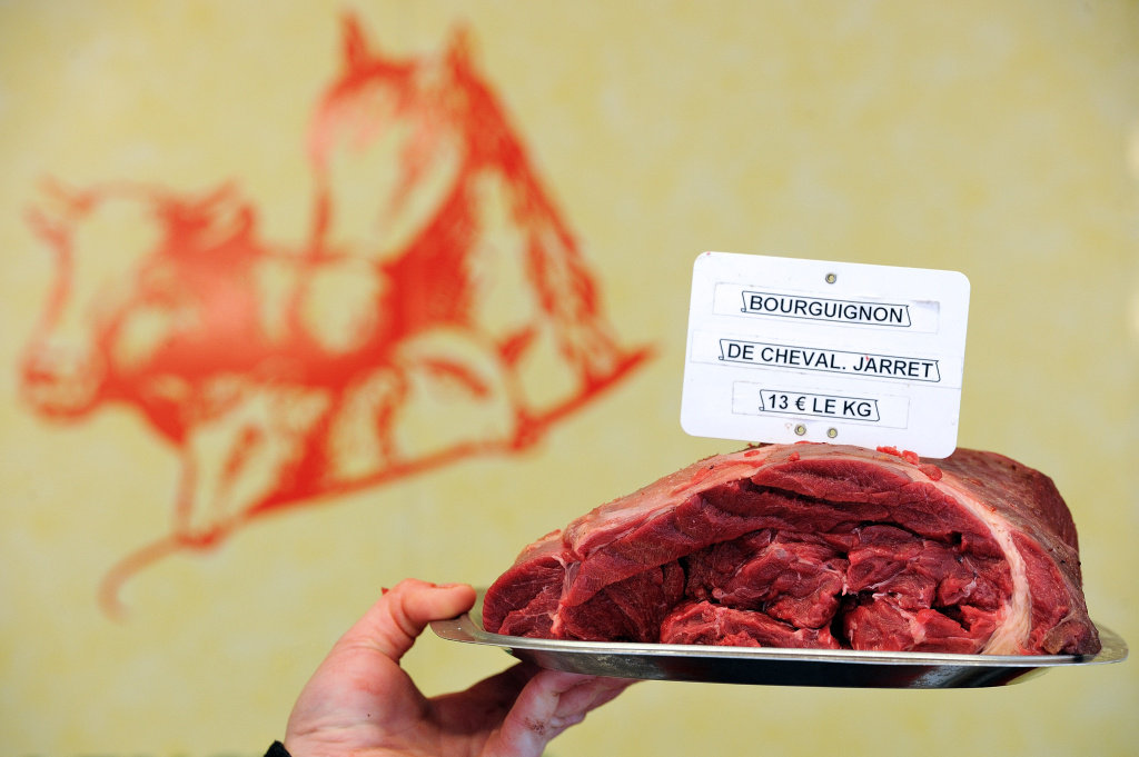 A butcher holds a piece of horse meat at a horse butchery in Anzin, northern France, on February 22, 2013.
