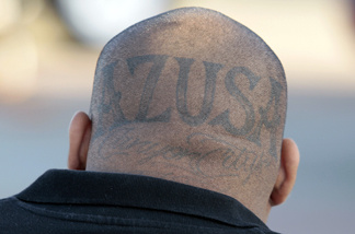"A suspect has ""Azusa Canyon City"" tattooed on the back of his head as members of a Azusa, Calif. gang are processed following an early-morning raid, at the at Irwindale Speedway in Irwindale, Calif., Tuesday, June 7, 2011. The Latino gang conspired to rid the Southern California city of its black residents through threats and violence dating back to the early 1990s, according to an indictment."