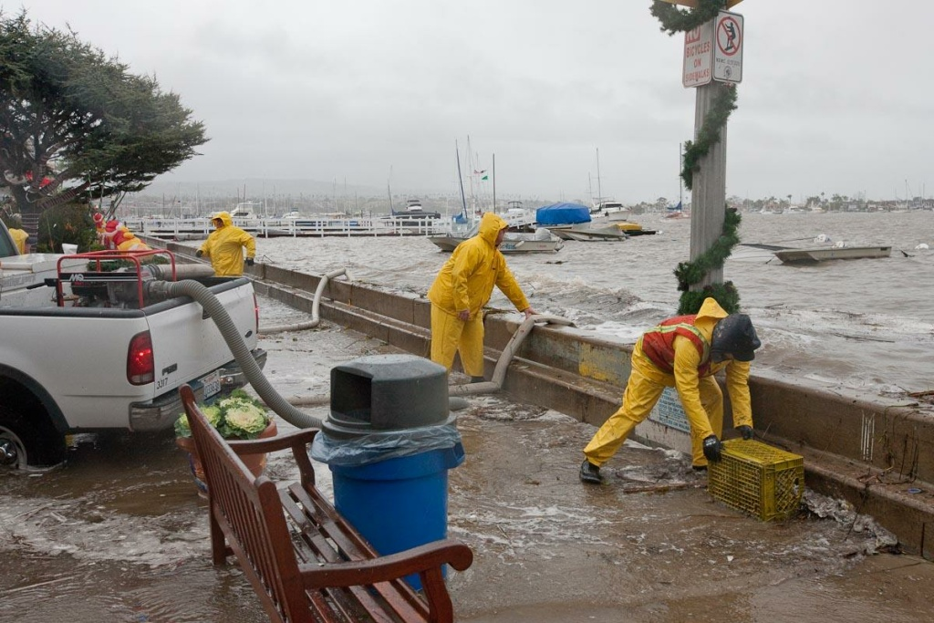 Newport Beach workers pump water that overtopped the seawalls on Balboa Island on Dec. 22, 2010. High tides and storm surges occasionally cause flooding on the island, but sea level rise threatens to make it a more frequent phenomenon. The city plans to extend the island's seawalls by 9 inches as a short-term fix.