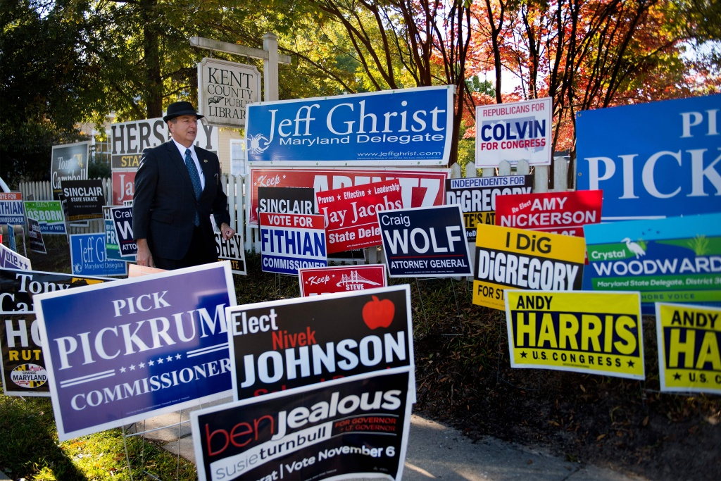 Mark Mumford, Clerk of the Circuit Court for Kent County, walks through a mass of political placards as he arrives to check on voter turn out in Maryland's early voting at the Kent County Public Library.