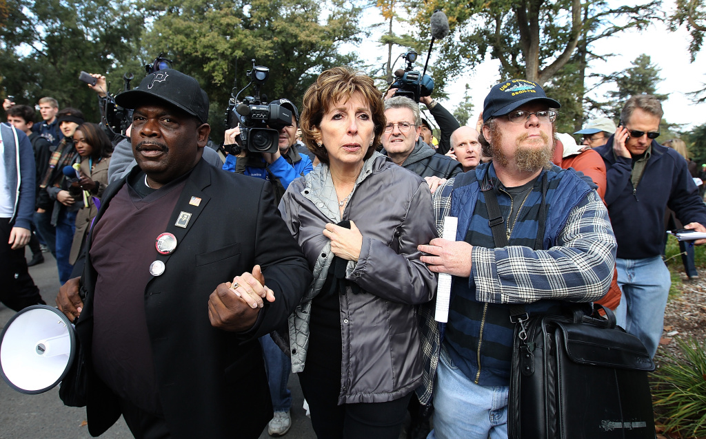 DAVIS, CA - NOVEMBER 21:  UC Davis Chancellor Linda Katehi (C) is escorted to a car after she spoke to Occupy protestors during a demonstration at the UC Davis campus on November 21, 2011 in Davis, California. Thousands of Occupy protestors staged a demonstration on the UC Davis campus to protest the UC Davis police who pepper sprayed students who sat passively with their arms locked during an Occupy Wall Street demonstration on November 18.  (Photo by Justin Sullivan/Getty Images)