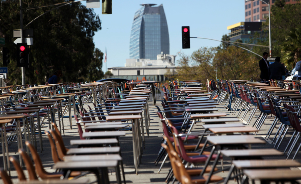 School desks placed by parents, district graduates and activists block a street in front of the Los Angeles Unified School District headquarters in a demonstration against student dropout rates Tuesday, April 8, 2014, in downtown Los Angeles. Protest organizers say the 375 desks are there to represent the 375 students who drop out of the district every week during the school year.