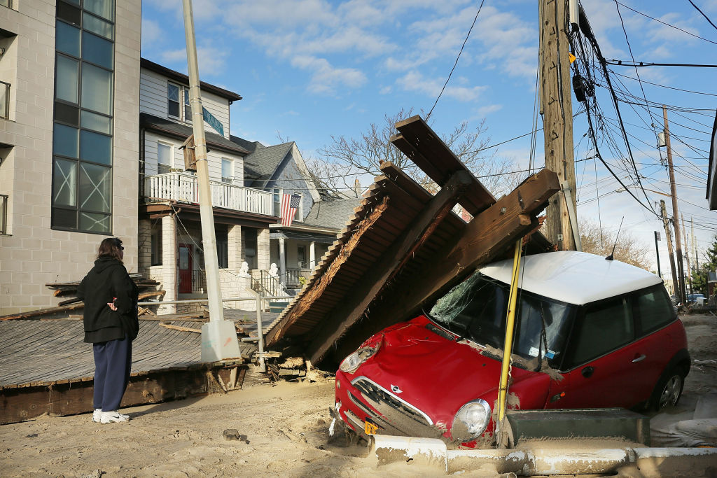 A woman looks at damage in the Rockaway neighborhood where the historic boardwalk was washed away during Hurricane Sandy on October 31, 2012 in the Brooklyn borough of New York City. With the death toll currently at 55 and millions of homes and businesses without power, the US east coast is attempting to recover from the affects of floods, fires and power outages brought on by Hurricane Sandy. JFK airport in New York and Newark airport in New Jersey expect to resume flights on Wednesday morning and the New York Stock Exchange commenced trading after being closed for two days.