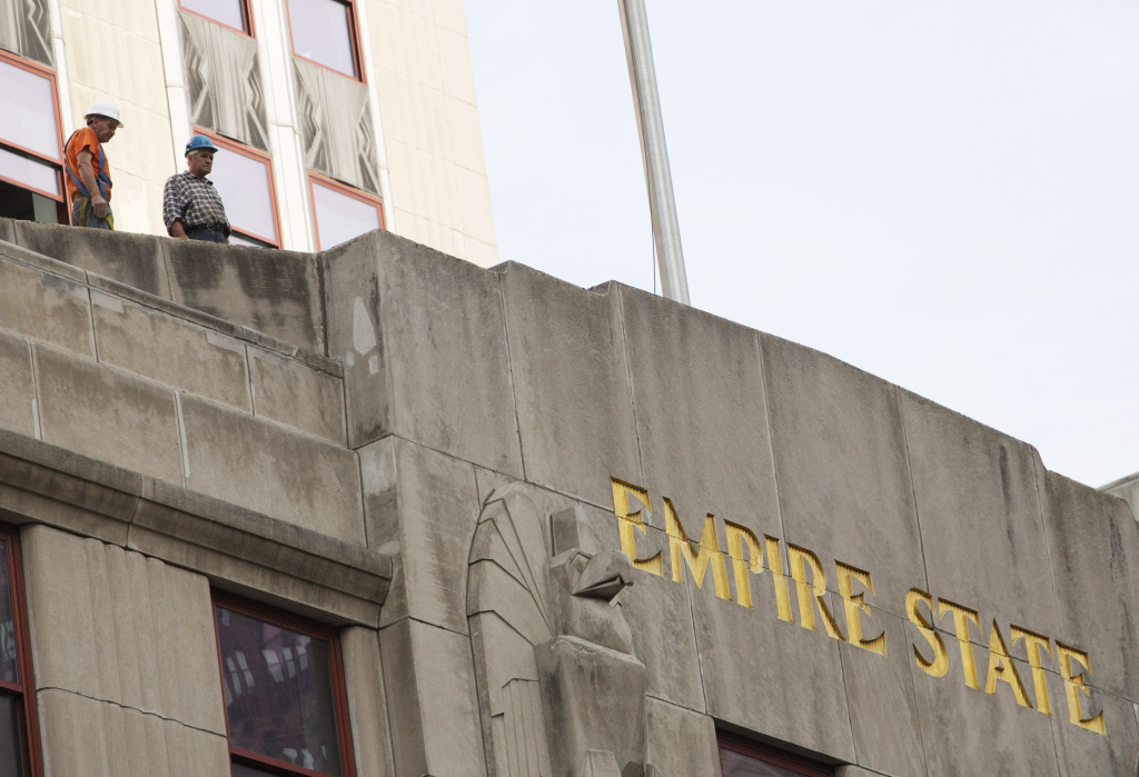Workers look over the scene of a shooting near the Empire State Building August 24, 2012 in New York City. According to reports, two people are dead, including the suspected shooter, and eight people were wounded in the morning shooting that is being described as stemming from a workplace dispute near the Empire State Building.