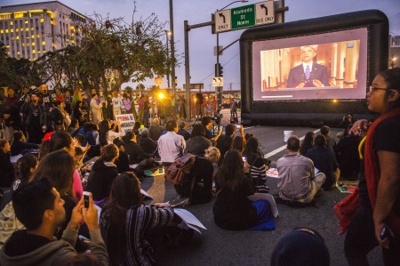 Onlookers watch as President Obama is shown on a projector near the intersection of Alameda St. and the 101 freeway in downtown Los Angeles last month, when he addressed the nation on his new immigration plan that could provide temporary legal status and work permits for millions. His executive order has already brought strong backlash from the right, but there's also pressure from the left to do more.