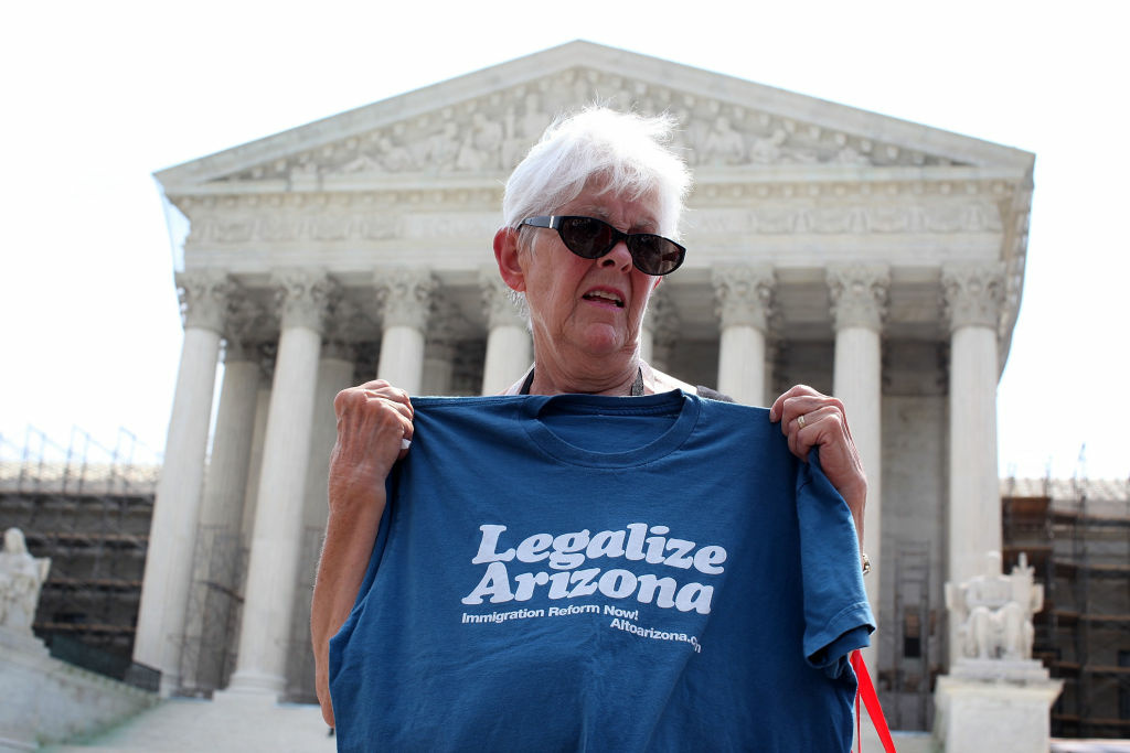Jane Pauk of Phoenix, Arizona, shows her support in front of the U.S. Supreme Court after the court announced an immigration law ruling June 25, 2012 in Washington, DC. The Supreme Court has struck down three parts of the Arizona anti-illegal immigration law, but upheld the controversial