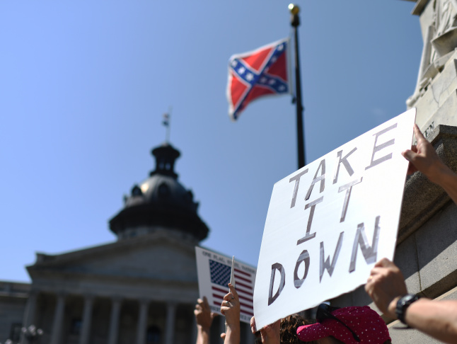 Protesters hold a sign during a rally to take down the Confederate flag at the South Carolina Statehouse, Tuesday, June 23, 2015, in Columbia, South Carolina. For years, South Carolina lawmakers refused to revisit the Confederate flag on Statehouse grounds, saying the law that took it off the dome was a bipartisan compromise, and renewing the debate would unnecessarily expose divisive wounds. The shooting deaths of nine people at a black church in Charleston, S.C., have reignited calls for the Confederate flag flying on the grounds of the Statehouse in Columbia to come down.