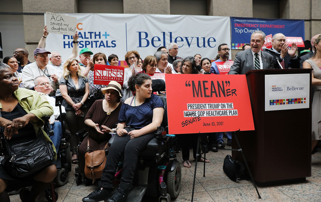 Doctors, nurses, patients and activists listen to Senate Minority Leader Chuck Schumer, D-N.Y., speak about Senate Republicans' health care bill on Friday at Bellevue Hospital in New York City. Schumer has vowed to help defeat the legislation, which the Congressional Budget Office scored on Monday.