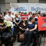 Doctors, nurses, patients and activists listen to Senate Minority Leader Chuck Schumer, D-N.Y., speak about Senate Republicans' health care bill on Friday at Bellevue Hospital in New York City. Schumer has vowed to help defeat the legislation, which the C