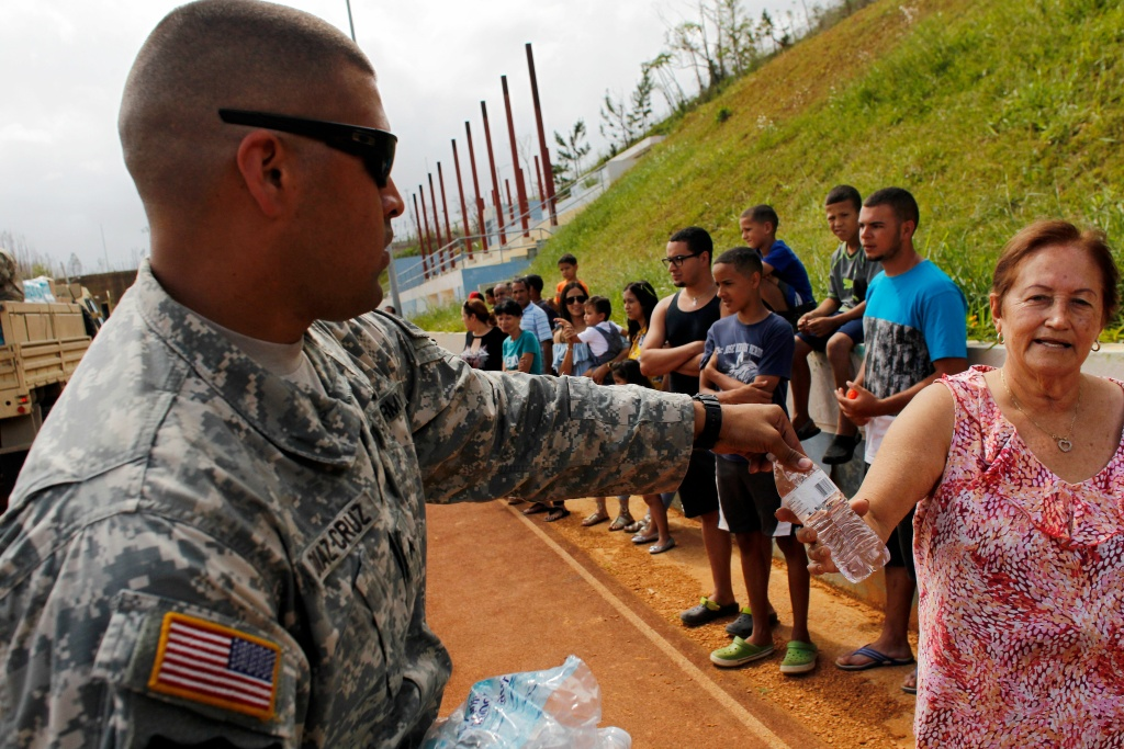 A U.S. Army serviceman gives bottled water to residents affected by Hurricane Maria in Barranquitas, Puerto Rico, on October 23, 2017.